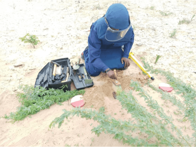 Searcher excavating ERW detected on the spot using Schonstedt UXO Locator (Magnetic Locator) in Daynile, Somalia. Photo Credit: UNMAS Somalia